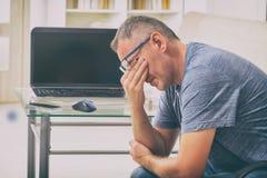 El hombre cansado del freelancer que frota el suyo observa Fotos de archivo libres de regalías