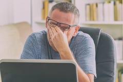 El hombre cansado del freelancer que frota el suyo observa Imagen de archivo