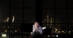 El hombre cansado del programador está trabajando en la oficina en horas extras tarde en la noche Saca sus vidrios y frota sus oj metrajes