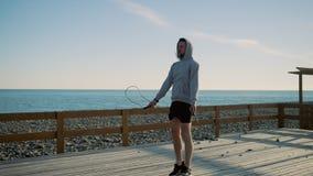 El hombre cansado está lanzando la cuerda que salta durante ejercicio en orilla de mar en d3ia metrajes