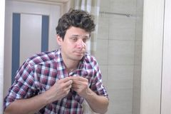 El hombre cansado soñoliento con una resaca por la mañana en el cuarto de baño sujeta su camisa y se pone en orden imagen de archivo libre de regalías