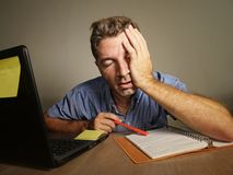 El hombre cansado y agotado soñoliento que trabajaba en la contabilidad de ordenador portátil que tomaba notas sobre la libreta t imágenes de archivo libres de regalías