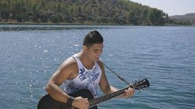 El hombre canta una canción con una guitarra metrajes