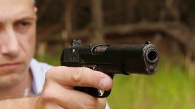 El hombre carga el arma y los lanzamientos Primer del arma y la cara del hombre en el fondo almacen de metraje de vídeo