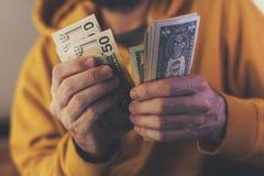 El hombre casual está contando billetes de banco americanos del dólar imagen de archivo