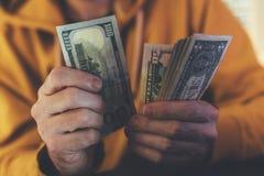El hombre casual está contando billetes de banco americanos del dólar fotografía de archivo libre de regalías