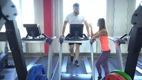 El hombre caucásico barbudo gordo camina en la rueda de ardilla en el gimnasio, la muchacha que el instructor supervisa la correc almacen de metraje de vídeo