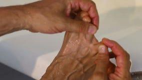 El hombre caucásico blanco adulto comprueba el pie de atletas entre los dedos del pie en baño Hongo de pie del enfoque entre los  metrajes