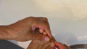El hombre caucásico blanco adulto comprueba el pie de atletas entre los dedos del pie en baño Hongo de pie del enfoque entre los  almacen de metraje de vídeo