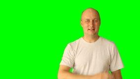 El hombre caucásico blanco adulto que ríe y hace gestos con la pantalla verde Línea pantalla virtual del drenaje del golpecito de metrajes