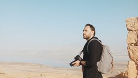 El hombre caucásico disfruta de panorama asombroso del mar muerto El fotógrafo emocionado se coloca en el top de la montaña con l almacen de video