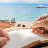 El hombre caucásico está escribiendo idea, el mensaje o la letra del sime en su libreta por la pluma mientras que él que se sient Fotos de archivo