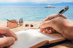 El hombre caucásico está escribiendo idea, el mensaje o la letra del sime en su libreta por la pluma mientras que él que se sient Imagenes de archivo