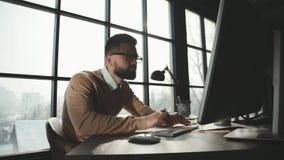 El hombre caucásico está trabajando en el ordenador portátil en la oficina del desván del estilo metrajes