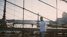 El hombre caucásico feliz se coloca solamente en el puente de Brooklyn que parece ausente y que usa la pulsera de reloj elegante  metrajes