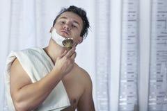 El hombre caucásico hermoso joven comienza a afeitar con el cepillo y la espuma, estilo del vintage del viejo peluquero Mirada se foto de archivo libre de regalías