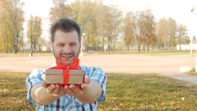 El hombre caucásico joven elegante y de moda agradable mira en la cámara y da una caja con un regalo, cámara lenta, espacio de la almacen de video