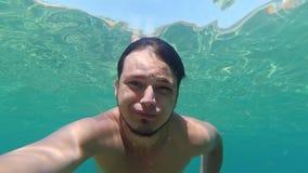 El hombre caucásico nada bajo el agua en el mar el vacaciones de verano metrajes