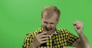 El hombre caucásico usando smartphone y celebra hacer sí gesto metrajes