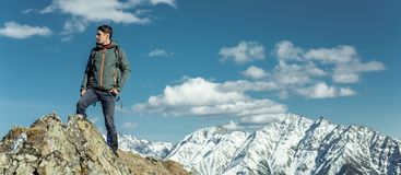 El hombre celebra el éxito que se coloca en el fondo de montañas nevosas Concepto de motivación y logro de sus metas foto de archivo libre de regalías