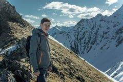 El hombre celebra el éxito que se coloca en el fondo de montañas nevosas Concepto de motivación y logro de sus metas fotografía de archivo libre de regalías
