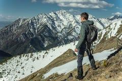 El hombre celebra el éxito que se coloca en el fondo de montañas nevosas Concepto de motivación y logro de sus metas foto de archivo