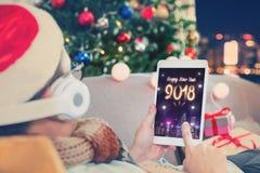El hombre celebra los fuegos artificiales del Año Nuevo 2018 con la tableta, gente feliz l Imágenes de archivo libres de regalías