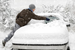 El hombre cepilla nieve de su coche Imagen de archivo