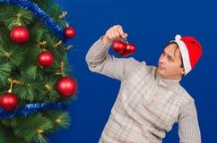 El hombre cerca de un árbol elegante del Año Nuevo mira los juguetes Fotos de archivo libres de regalías