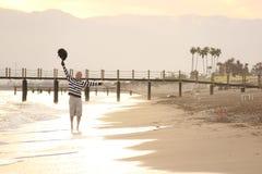 El hombre cerca del mar aumenta las manos con una mochila para arriba imagen de archivo libre de regalías