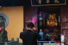 El hombre chino está rogando en un templo budista y palillos ardientes del incienso Foto de archivo