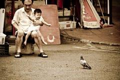 El hombre chino lleva a un niño que sea excitado por un pájaro fotos de archivo libres de regalías