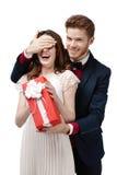 El hombre cierra ojos de su novia para dar un presente en rectángulo rojo Fotografía de archivo libre de regalías