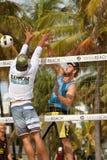 El hombre clava la bola más allá del defensor en partido de balonvolea de Miami Beach Fotos de archivo libres de regalías