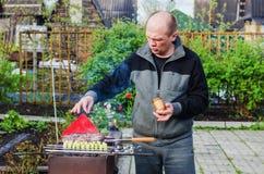 El hombre cocina la barbacoa Fotos de archivo
