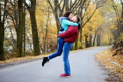 El hombre coge en sus brazos el suyo querido en un día maravilloso del otoño Foto de archivo