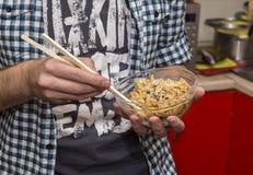 El hombre come el arroz frito con los palillos para el sushi Imagen de archivo