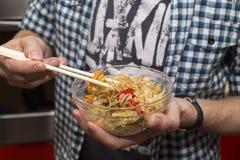 El hombre come el arroz frito con los palillos para el sushi Fotografía de archivo