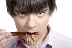 El hombre come el calamar Fotografía de archivo libre de regalías