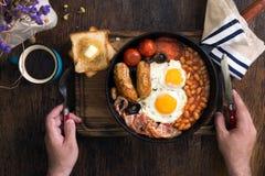 El hombre come el desayuno inglés en una tabla de madera oscura Imagen de archivo libre de regalías