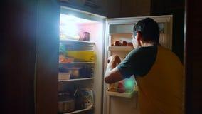 El hombre come hambre y glotonería del refrigerador en la noche el hombre considera en el refrigerador la noche glotonería de la  metrajes