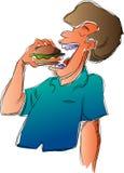 El hombre come la hamburguesa Foto de archivo libre de regalías
