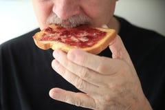 El hombre come la parte de la tostada con el atasco imagen de archivo libre de regalías