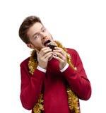 El hombre come la pequeña torta Imagen de archivo libre de regalías