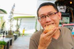 El hombre come la pizza Imagen de archivo libre de regalías