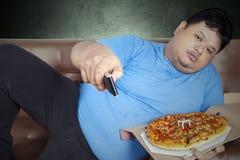 El hombre come la pizza mientras que ve TV 1 Imágenes de archivo libres de regalías