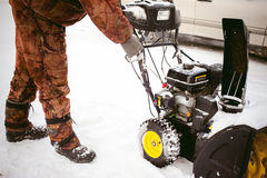 El hombre comienza el ventilador de nieve del motor fotos de archivo