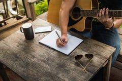 El hombre compone la canción y la guitarra del juego Foto de archivo