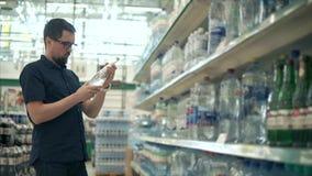 El hombre compra agua mineral en supermercado metrajes