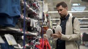 El hombre compra nuevas zapatillas de deporte almacen de metraje de vídeo